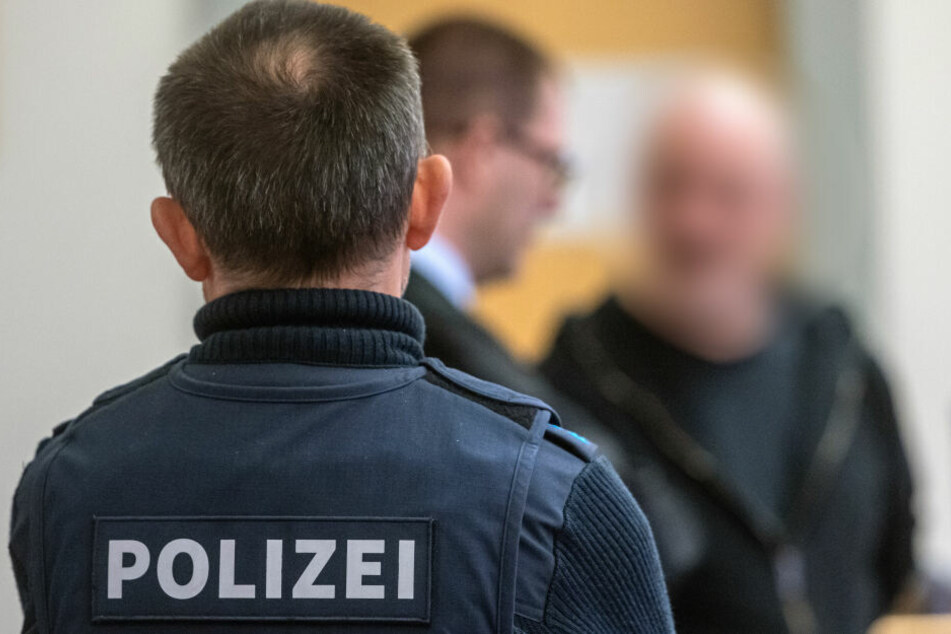 Der 51 Jahre alte Mann (im Hintergrund mit seinem Anwalt) soll in Straubing mit seinem Auto auf zwei auf der Straße stehende Polizisten zugerast sein, um einer Verkehrskontrolle zu entgehen.