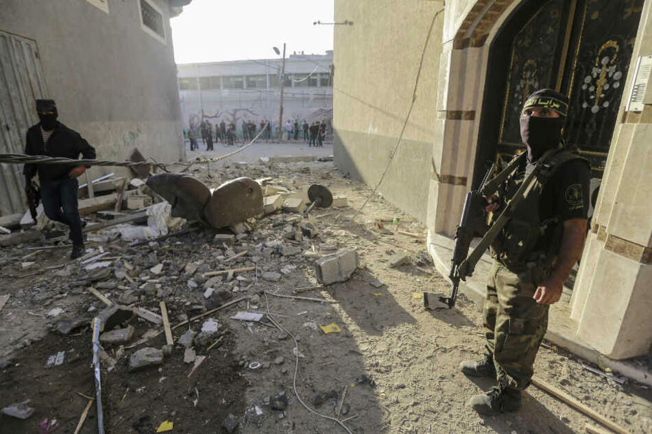Palästinensische Milizen stehen nach einem israelischen Luftangriff vor dem beschädigte Haus des islamischen Dschihad-Führers Baha Abu Al Ata Wache.