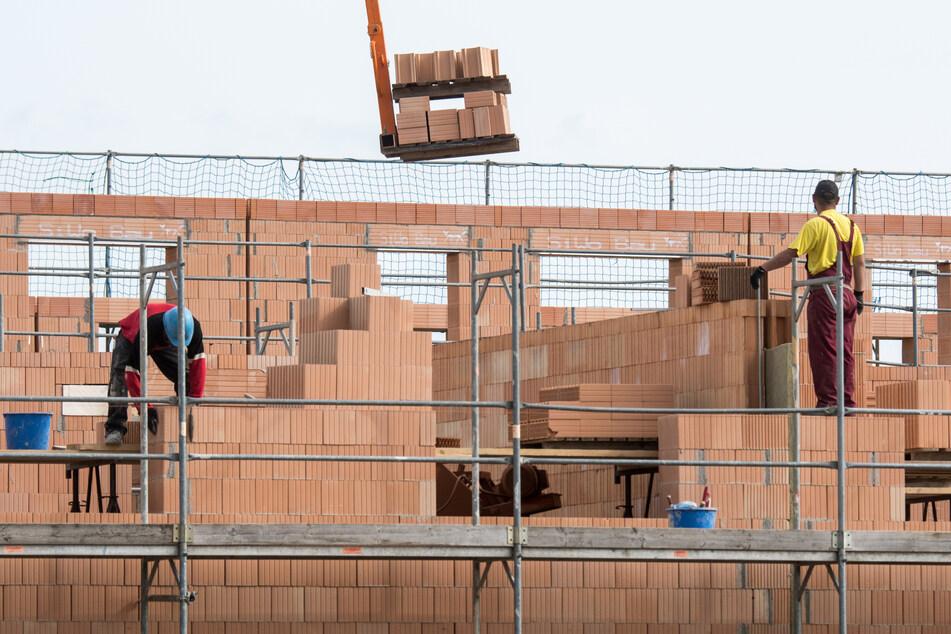 Maurer arbeiten am Rohbau von Reihenhäusern in einer Neubausiedlung. Eigenheime in Deutschland haben sich in der Corona-Krise erheblich verteuert.