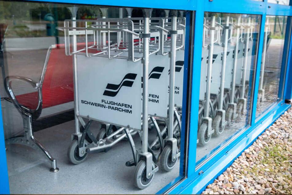 """Zeugen von großen Plänen: Gepäckwagen mit der Aufschrift """"Flughafen Schwerin-Parchim"""" in einem verschlossenen Abfertigungsgebäude."""