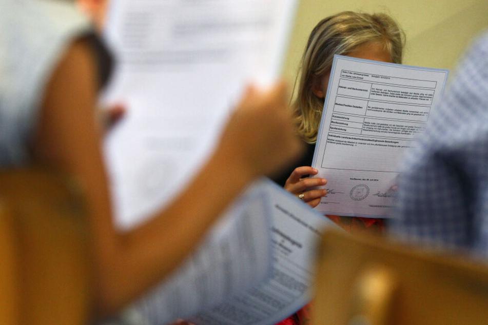 Schüler einer ersten Klasse sitzen in einer Grundschule und lesen ihre Zeugnisse.