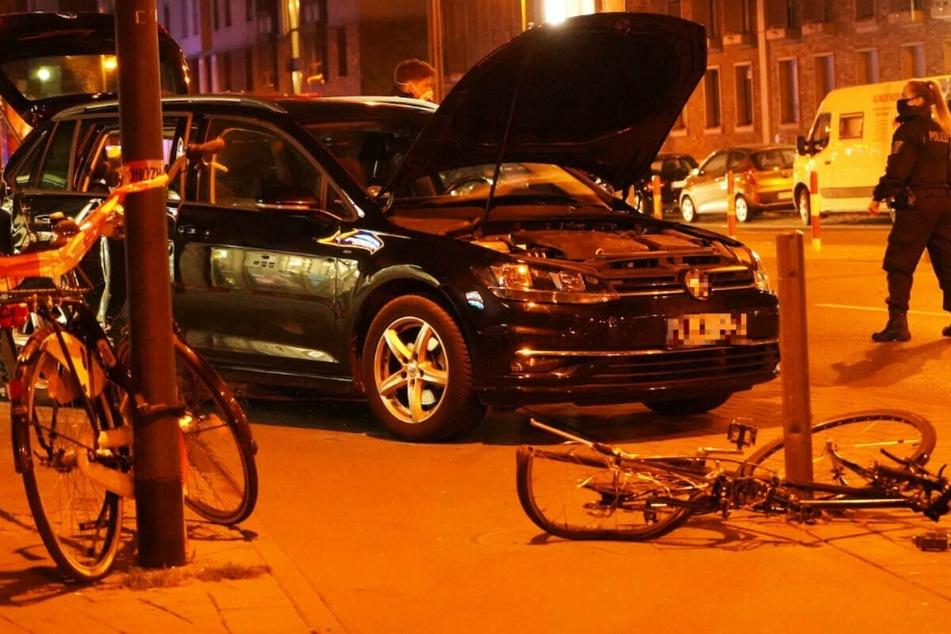 Das Foto zeigt ein schwarzes Auto sowie ein beschädigtes Fahrrad am Unglücksort in Frankfurt.