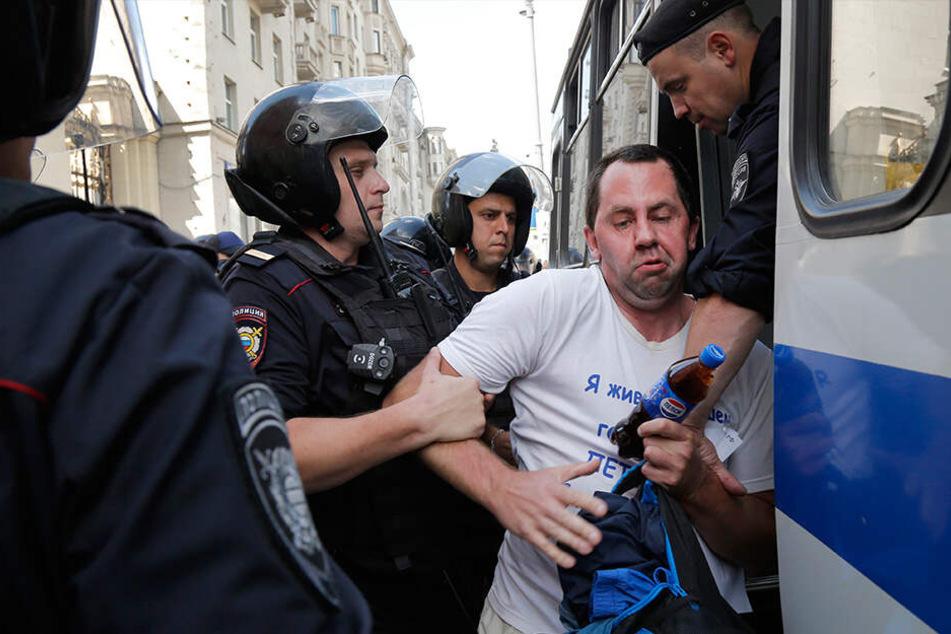 Polizeibeamte verhaften einen Mann, der bei der nicht genehmigten Kundgebung protestierte.