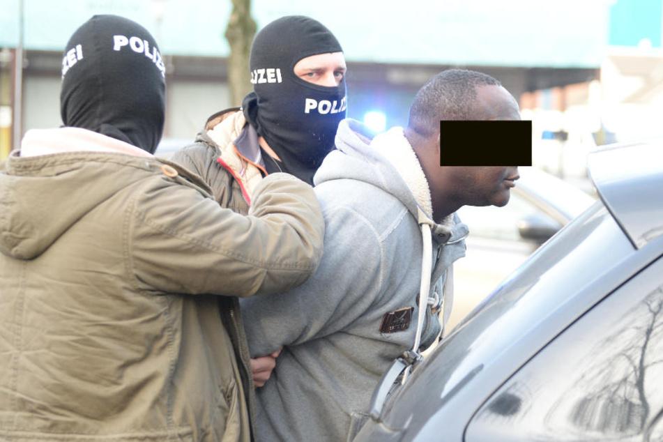 Maskierte Polizisten legen einem der Männer Handschellen an.
