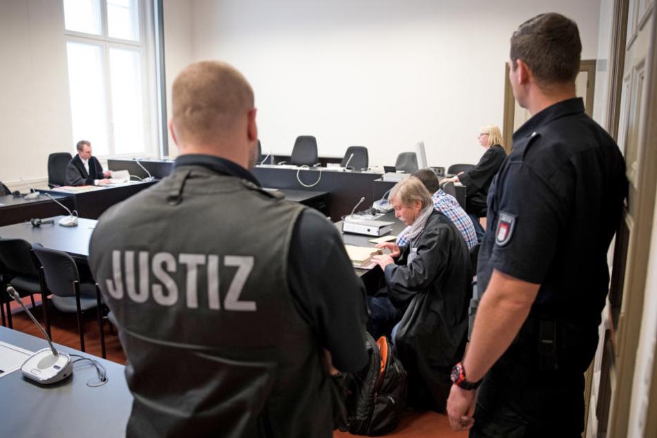 Rechtsanwalt Wilfried Behrendt (Mitte) und sein Mandant sitzen vor Prozessbeginn in einem Gerichtssaal im Strafjustizgebäude.