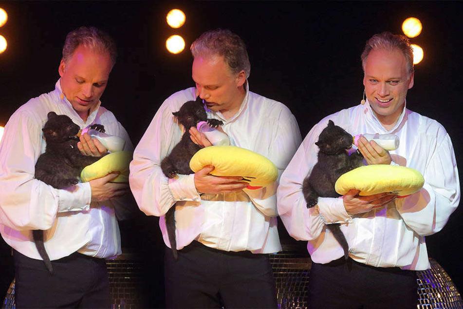 Magier André Sarrasani (45) gibt dem kleinen Panthermädchen die Flasche. Die schwarze Mieze ist so groß wie einen Hauskatze.