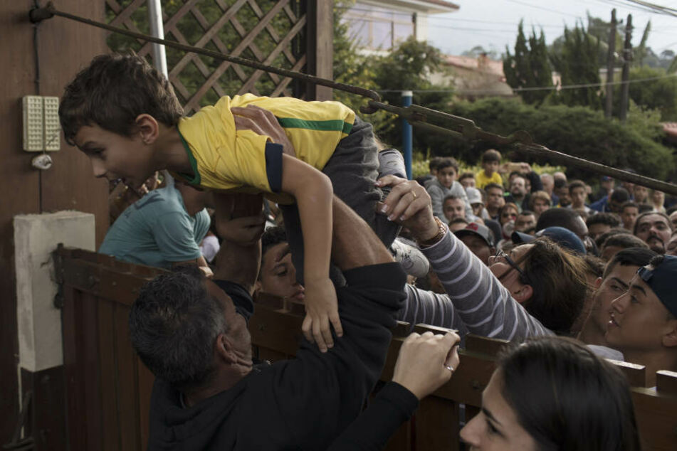 Ein Junge wird über das Tor des Trainingszentrums bei Granja Comary gehoben.