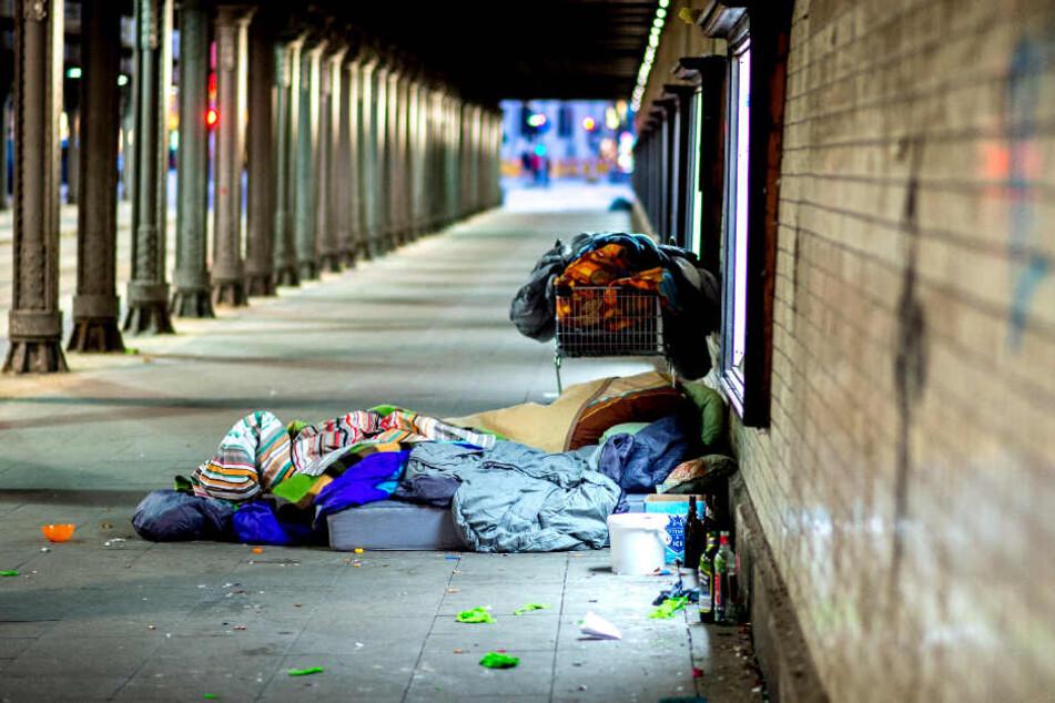 Ein Obdachloser hat sein Lager unter einer Brücke in einem Durchgang aufgeschlagen.