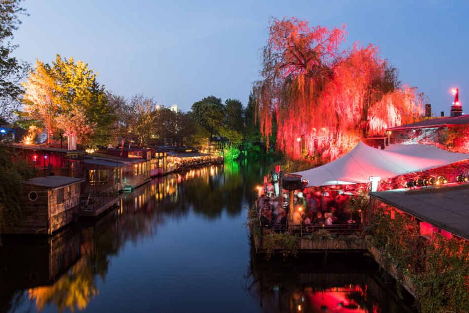 """Restaurants und Clubs am abendlich angeleuchteten Flutgraben. Rechts ist der """"Club der Visionäre"""" zu sehen."""