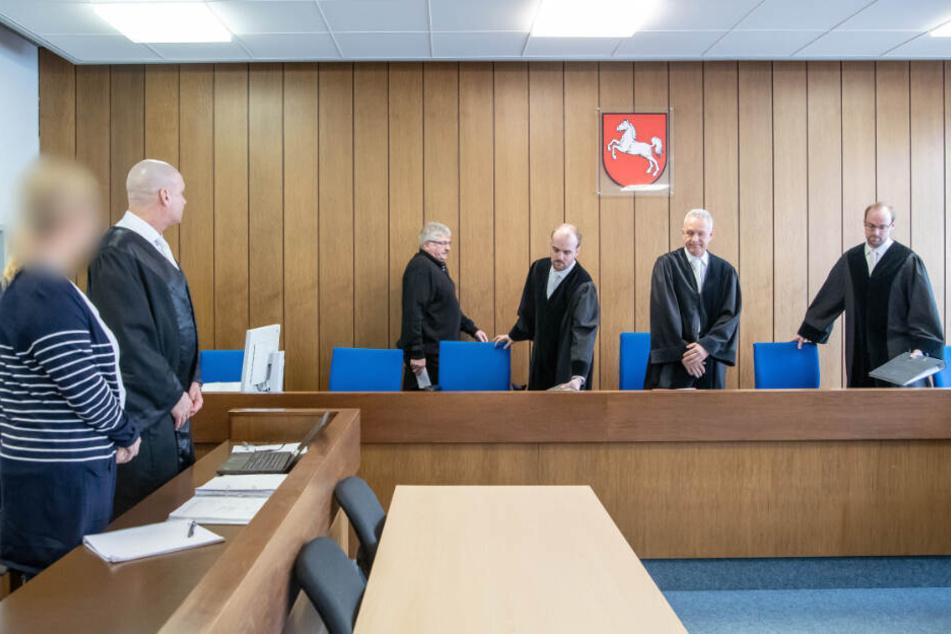 Während die Richter den Raum betreten, steht die Angeklagte (links) mit ihrem Anwalt vor Prozessbeginn im Gerichtssaal.