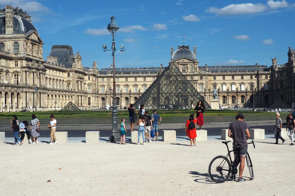 Touristen stehen im Jardin du Carrousel vor der Pyramide des Louvre-Museums.