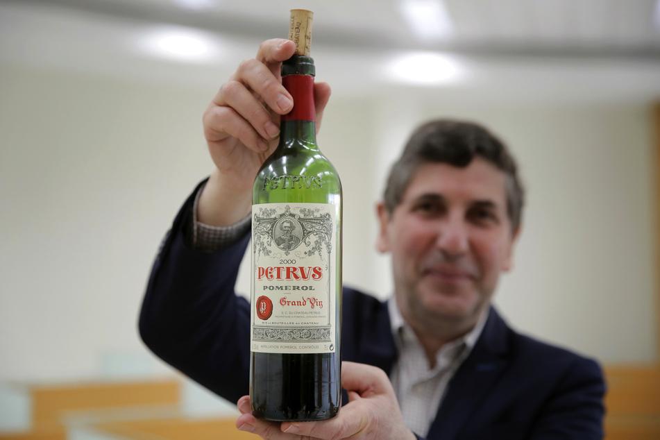 Philippe Darriet, Präsident des Instituts für Wein- und Rebenforschung und Chef-Önologe mit der Flasche Petrus-Rotwein, die ein Jahr lang an Bord der ISS um die Erde kreiste.