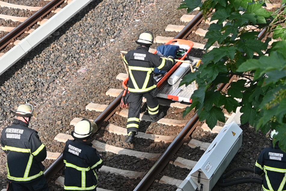Einsatzkräfte der Feuerwehr laufen in der Nähe der Unfallstelle über das Gleis.