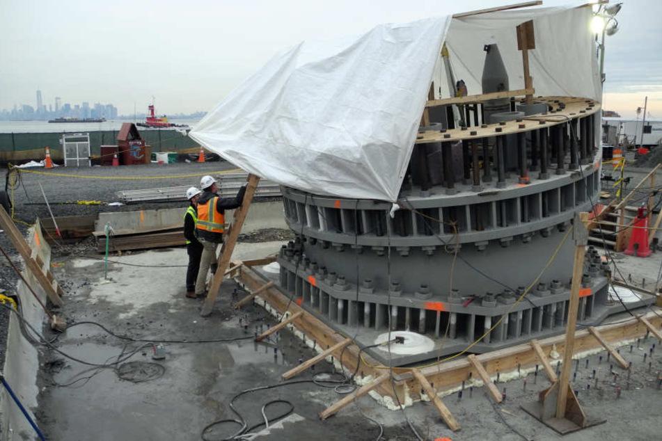"""Bauarbeiter arbeiten an einem Sockel für das Riesenrad """"New York Wheel"""", das im Jahr 2018 in Betrieb gehen sollte."""