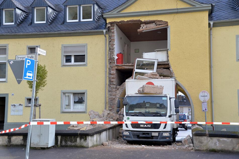 Ein Miet-LKW steckt in einer Hausdurchfahrt fest. Teile eines darüber gelegenen Mehrfamilienhauses sind dabei eingestürzt.