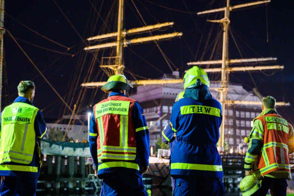Mitglieder von Feuerwehr und THW schauen zum historischen Segelschiff, das in Schräglage geraten ist.