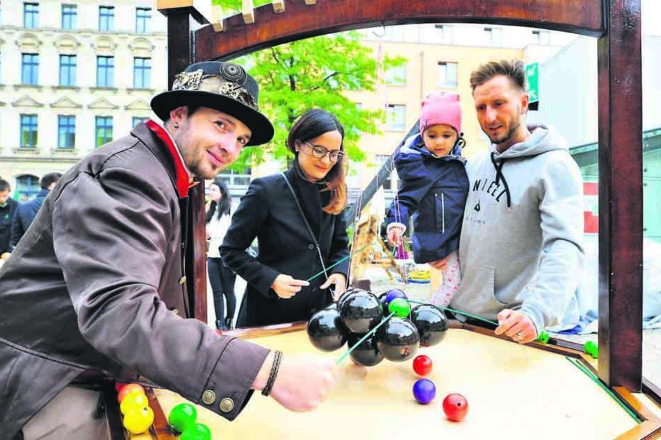 """Christian Mädler (34) alias """"Hanz Dampf"""" versucht sich hier mit Besuchern an  einem historischen Holzspiel."""