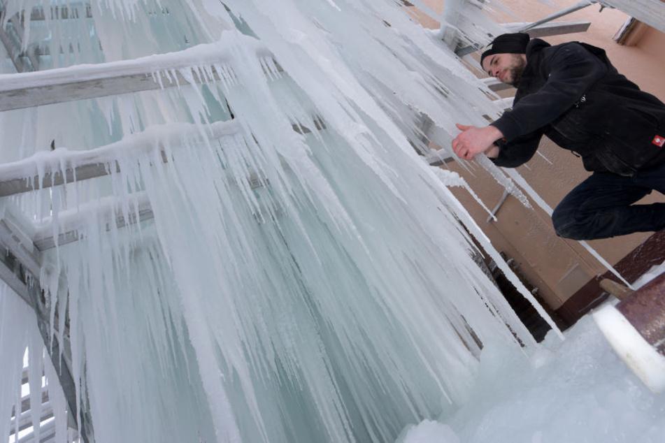 An dem etwa vier Meter hohen Eisgalgen wachsen lange Eiszapfen. Brauer Marcel Russe kontrolliert das Eis.