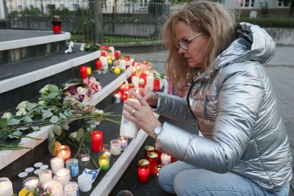 Ute Pfeil aus Düsseldorf legt Blumen auf die Treppe vor der Synagoge und entzündet eine Kerze.
