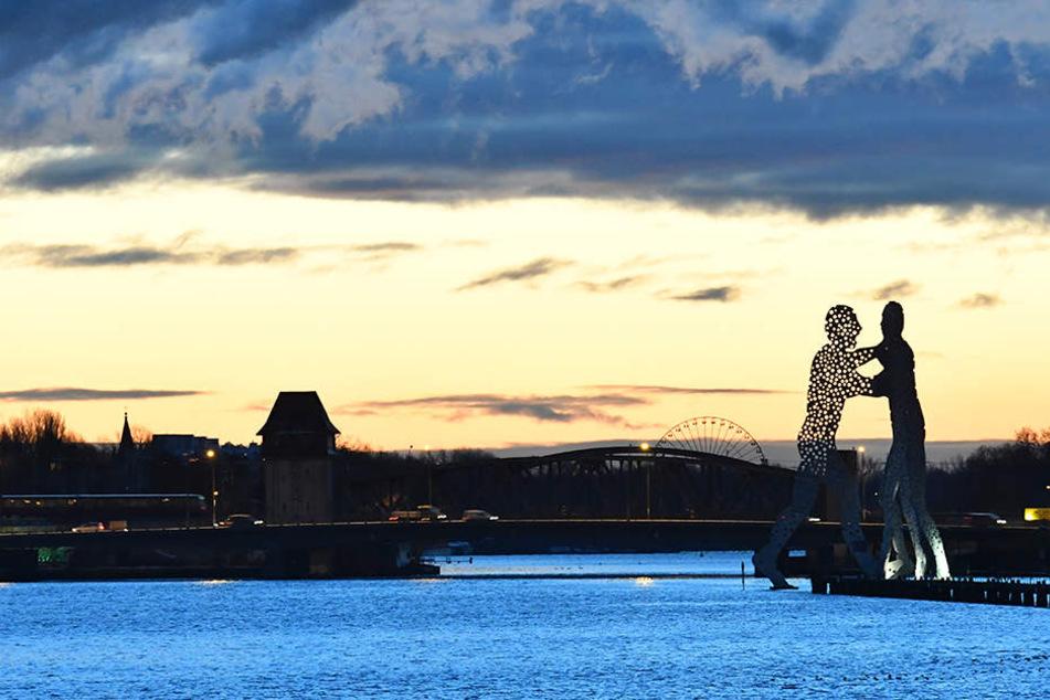 Farbenfroh zeigt sich in Berlin der Himmel über der Elsenbrücke und der Skulptur Molecule Man.