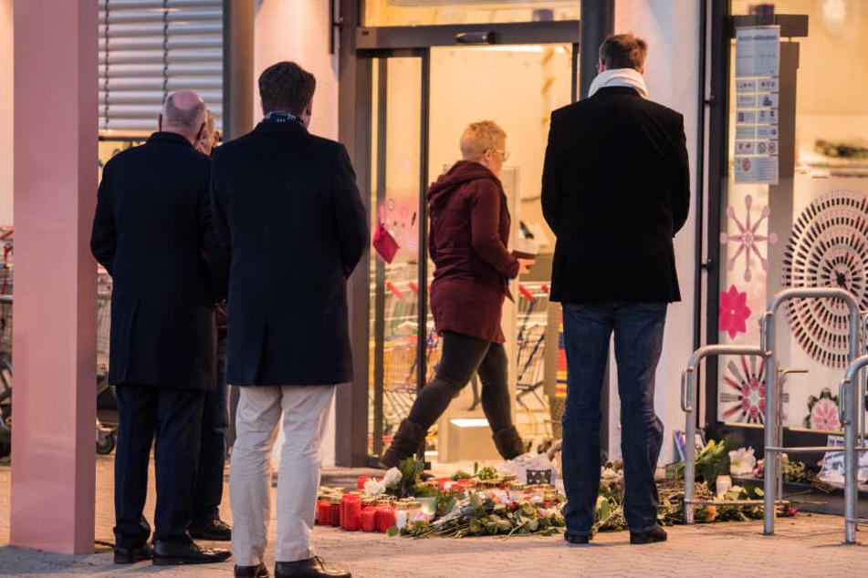 In einer Drogeriemarktfiliale in Kandel wurde die 15-Jährige erstochen. Nach der Tat trauern Menschen vor dem Laden.