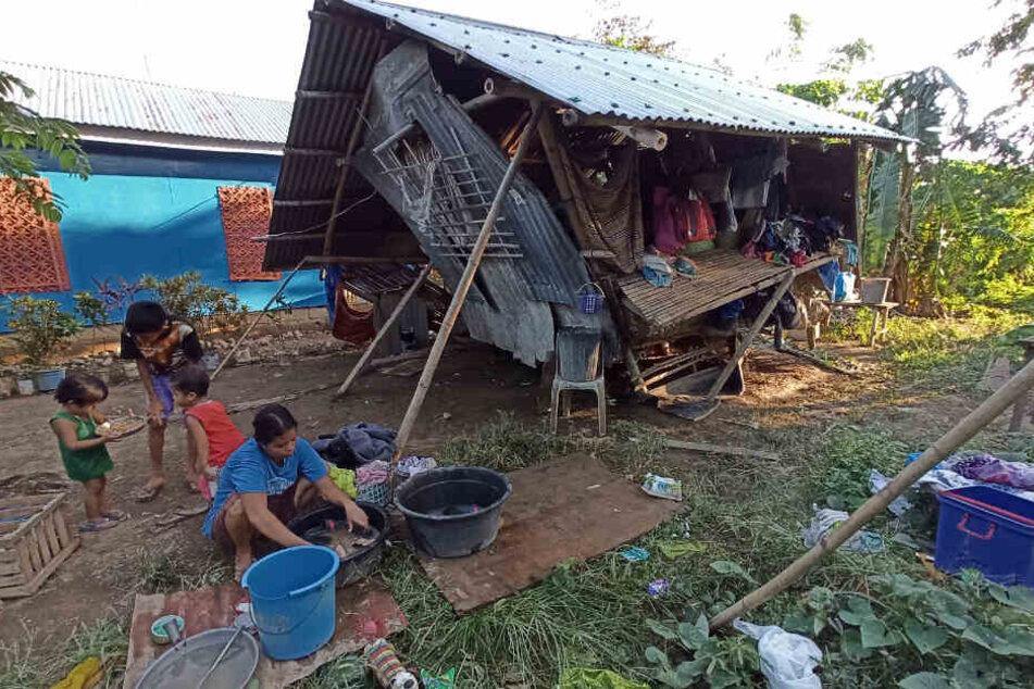 Die Bewohner eines Hauses halten sich im Freien auf, nachdem ihr Zuhause von dem Taifun «Phanfone» zerstört wurde.