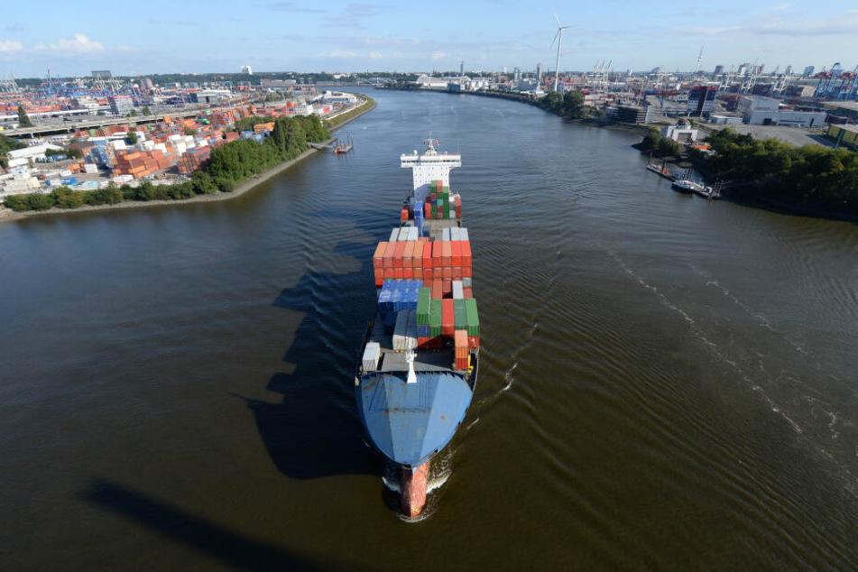 Ein großes Containerschiff ist auf der Elbe bei Hamburg unterwegs.