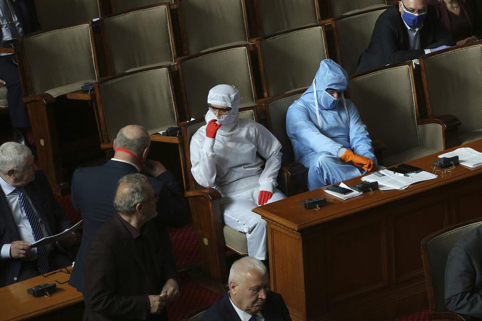 Politiker tragen während der Parlamentssitzung in der bulgarischen Nationalversammlung in Sofia Schutzanzüge.