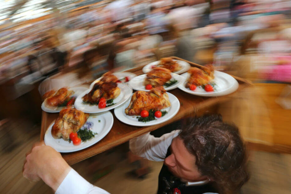 Ein Kellner trägt auf dem Oktoberfest Hendl auf einem Tablett.