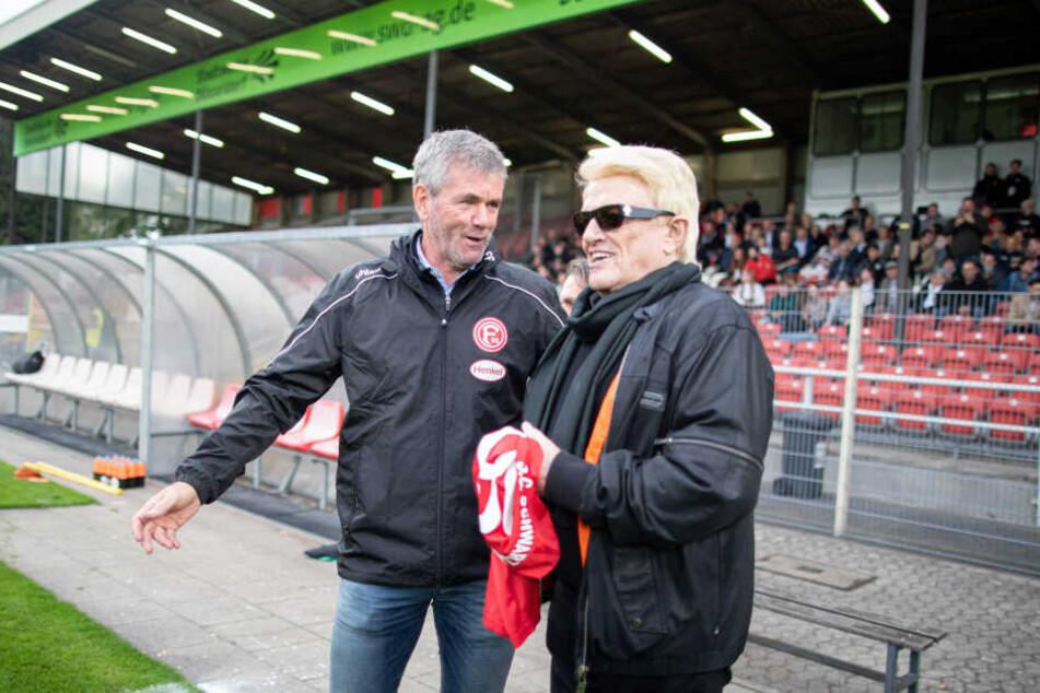 Heino (80) steht vor den Anstoß für das Benefizspiel auf dem Spielfeld neben Fortuna Trainer Friedhelm Funkel (65).