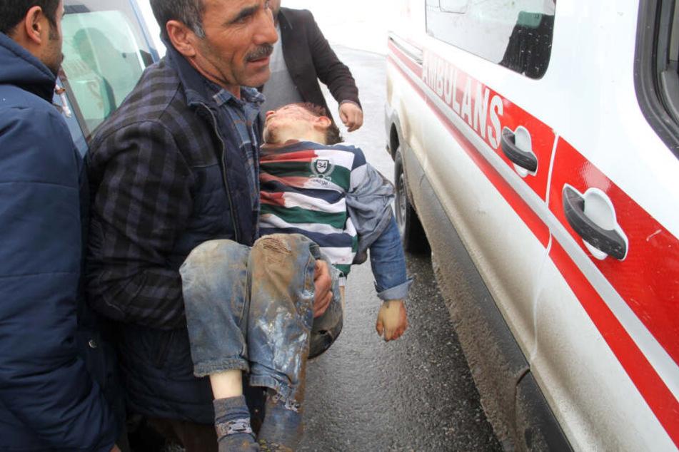 Ein Mann trägt einen verletzten Jungen zu einem Krankenwagen, nachdem ein Erdbeben Dörfer in der Provinz Van schwer erschüttert hat.