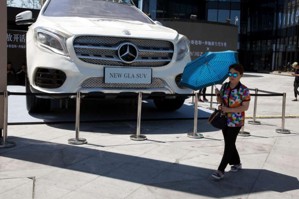 Eine Frau läuft in Peking an einem riesigen Modell des Mercedes GLA vorbei. In der chinesischen Stadt laufen nun die meisten Autos der Stuttgarter vom Band. (Archivfoto)