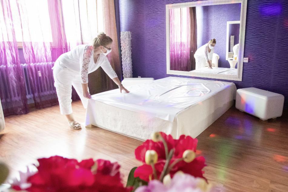 """Laura, Mitbetreiberin von """"Lauras Girls"""", richtet ein Bett in einem Arbeitszimmer des Bordells."""