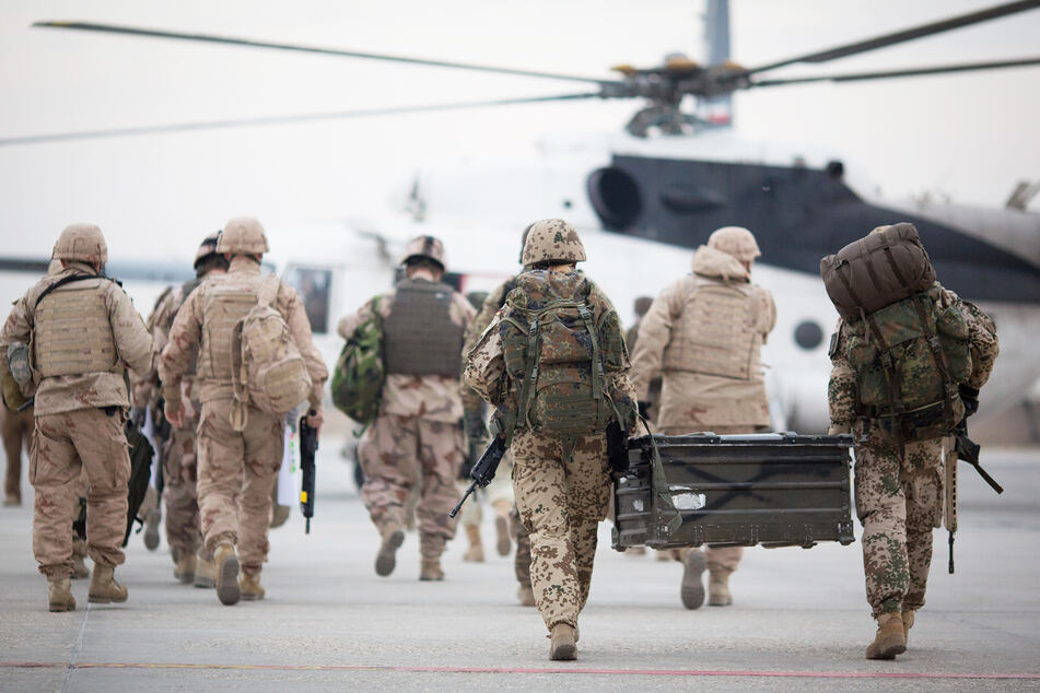 Bundeswehrsoldaten tragen auf dem Flughafen in Masar-i-Scharif zu einem wartenden Hubschrauber eine Feldkiste.