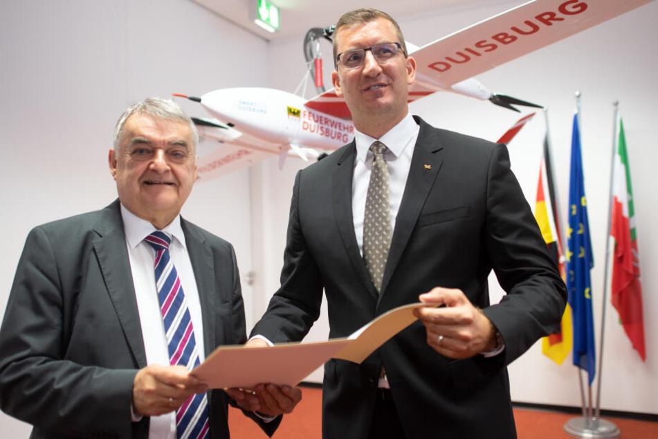 Herbert Reul (CDU,l), Innenminister von Nordrhein-Westfalen und Dennis Göge, Programmkoordinator für Sicherheitsforschung beim Deutschen Zentrum für Luft- und Raumfahrt (DLR), stehen vor einer Drohne der Feuerwehr Duisburg.