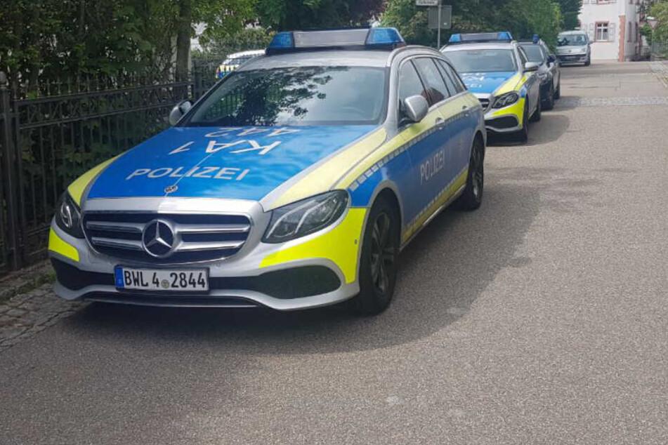 Mehrere Polizeifahrzeuge stehen in einer Straße.