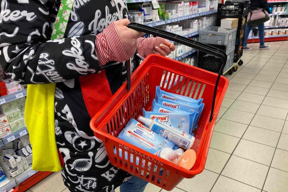 Eine Kundin hat Desinfektionsmittel und Hygiene-Reinigungstücher in der Drogerie gekauft.