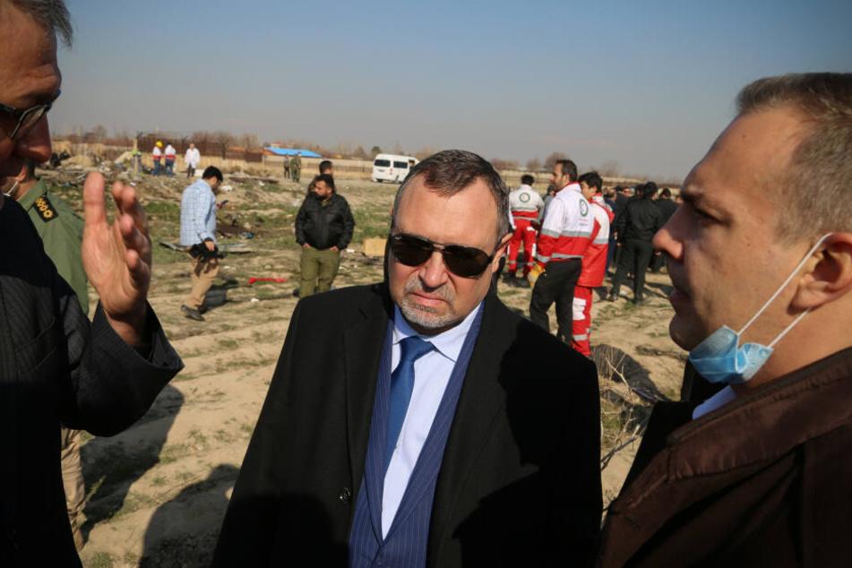 Sergej Burdiljak (Mitte), ukrainischer Botschafter im Iran, steht an der Absturzstelle der ukrainischen Passagiermaschine.