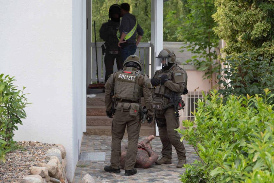 Spezialkräfte der Polizei mit einem der Tatverdächtigen.