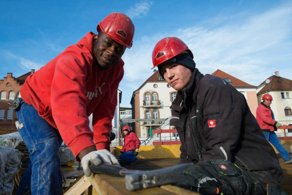 Vincent Ahondoh (l.) und Sven Hofmann, Auszubildende in der Bauwirtschaft auf einer Baustelle in Esslingen.