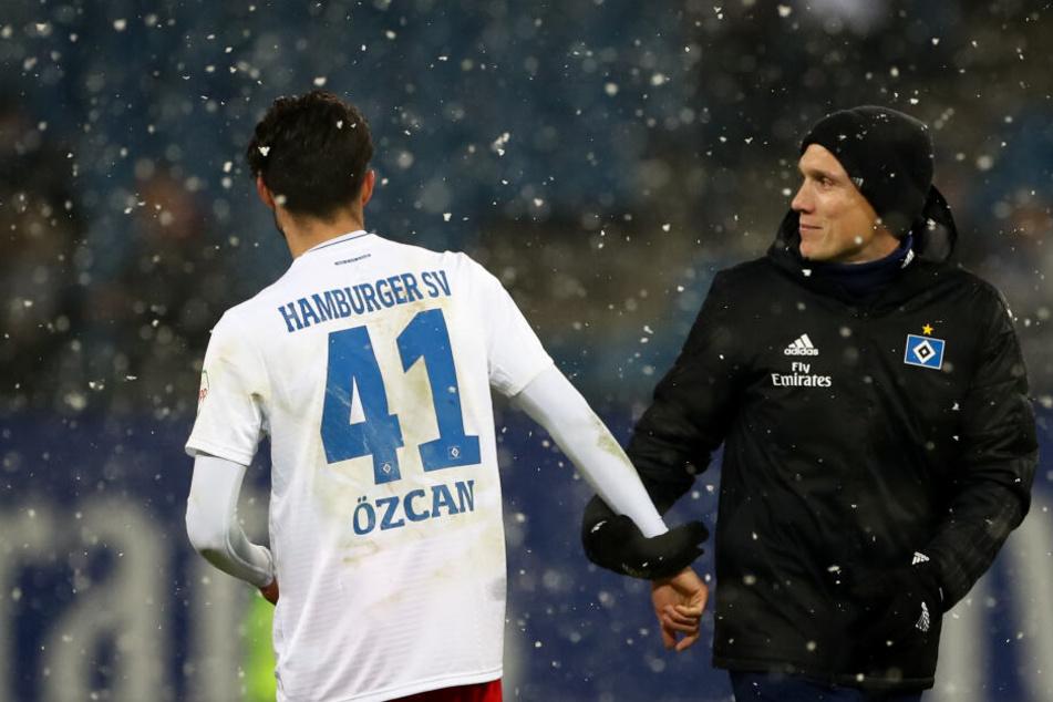 Am 19. Spieltag im Volksparkstadion stehen Hamburgs Berkay Özcan (links) und Trainer Hannes Wolf nach dem Spiel auf dem Platz, während es schneit.
