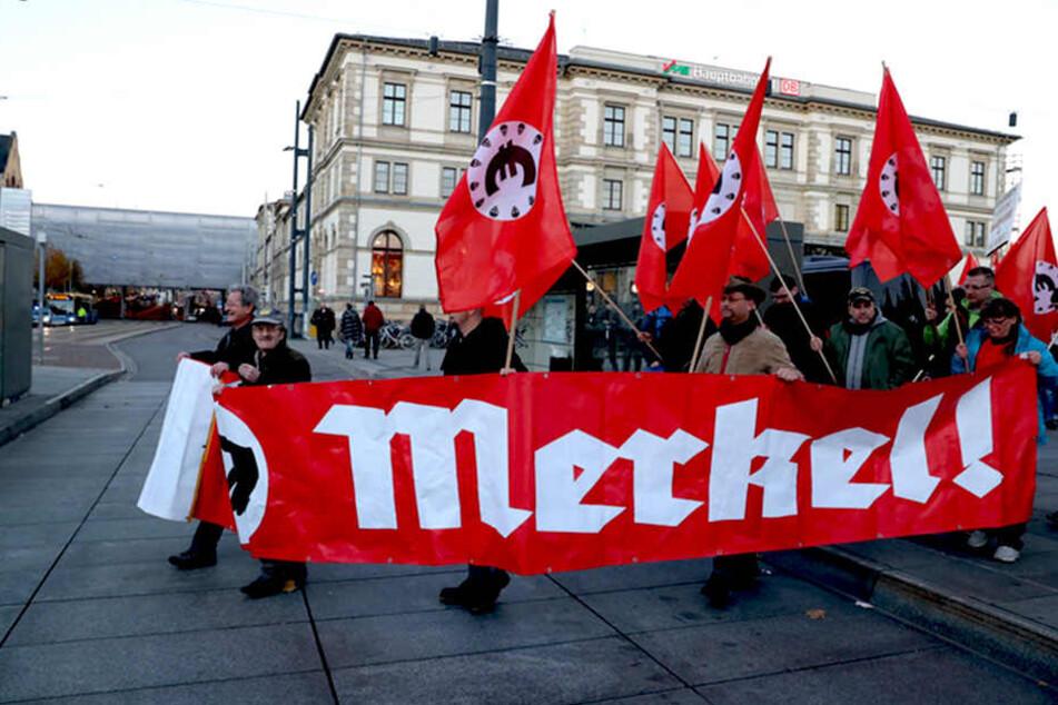 """Teilnehmer einer von der """"Merkeljugend"""" angemeldeten rechten Kundgebung mit einem Merkel-Transparent."""