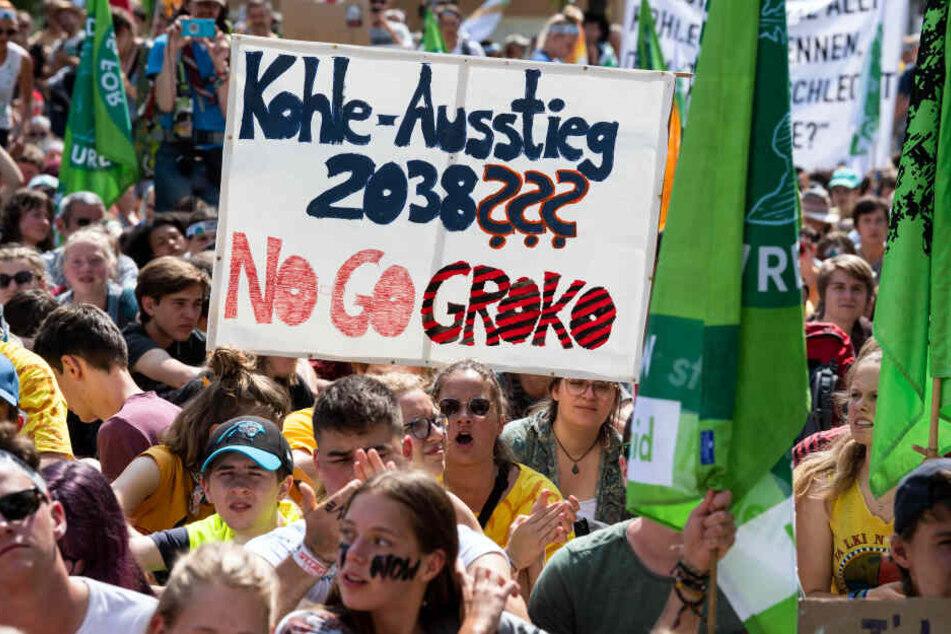 """""""Kohle Ausstieg 2038??? No Go Kroko"""" steht auf einem Protestplakat, das Demonstranten in die Höhe halten."""