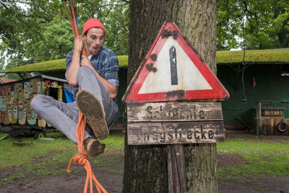 """Der Netzwerker Fynn Kliemann schwingt an einem Seil über seinen Kreativhof """"Kliemannsland"""" in Dorf (Niedersachsen)."""