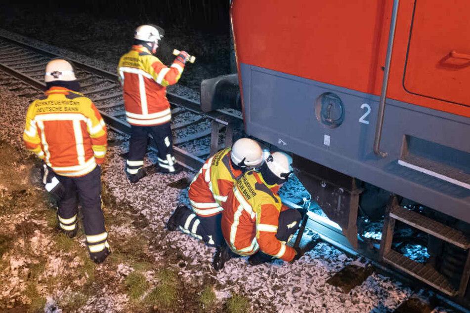 Einsatzkräfte der Feuerwehr überprüfen die Schäden am IC.