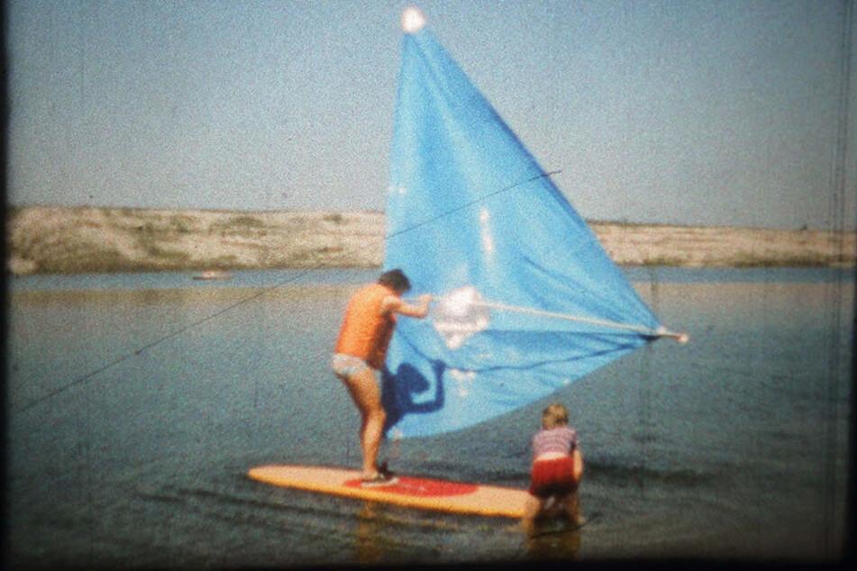 """Alles dicht? Halten Kleber und Segelnähte? Vater Wagner mit Sohn Falk beim Praxistest eines selbstgebauten """"Segelbretts"""" in Großkoschen am Senftenberger See."""