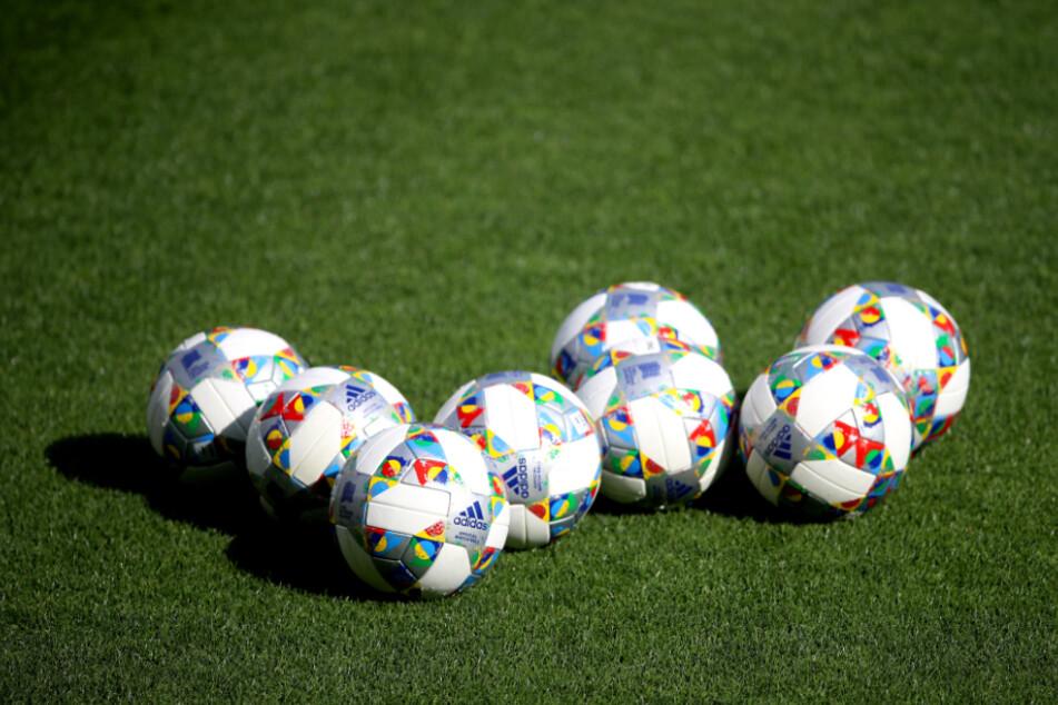 Mehrere Bälle liegen auf einem Fußballplatz (Symbolbild).