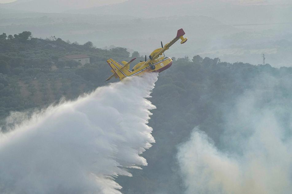Ein Canadair-Flugzeug wirft Wasser ab, um ein Feuer in der Nähe von Oristano auf der Insel Sardinien zu löschen