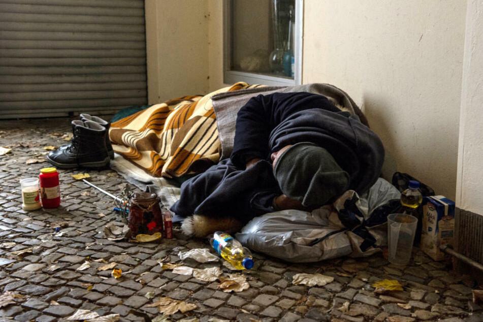 Ein Obdachloser liegt in einem Hauseingang. Die Berliner Stadtmission fordert in der Corona-Pandemie mehr Aufwärm-Möglichkeiten für Obdachlose am Tag. (Symbolfoto)