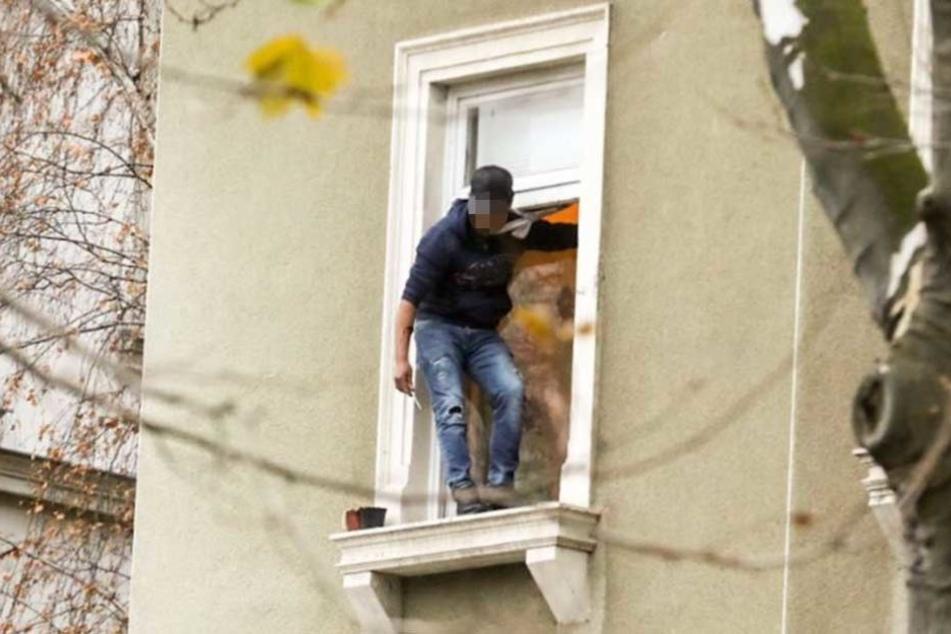 Der Mann steht im Fenster, in seiner rechten Hand hält er ein Messer.